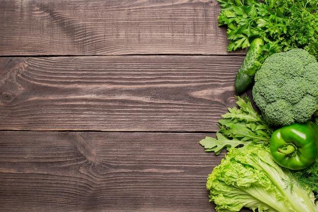 Quadro de legumes frescos verdes sobre fundo de madeira
