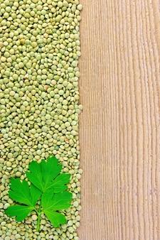 Quadro de lentilhas verdes com folha de salsa no lado esquerdo de tábuas de madeira