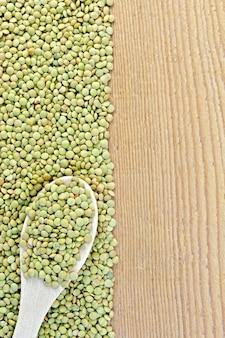 Quadro de lentilhas verdes com uma colher no lado esquerdo de tábuas de madeira
