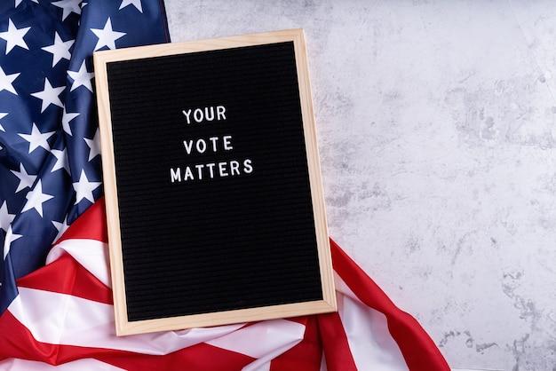Quadro de letras preto com o texto que seu voto importa com a bandeira americana sobre fundo de mármore branco