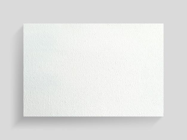 Quadro de lona branca no fundo da parede cinza.