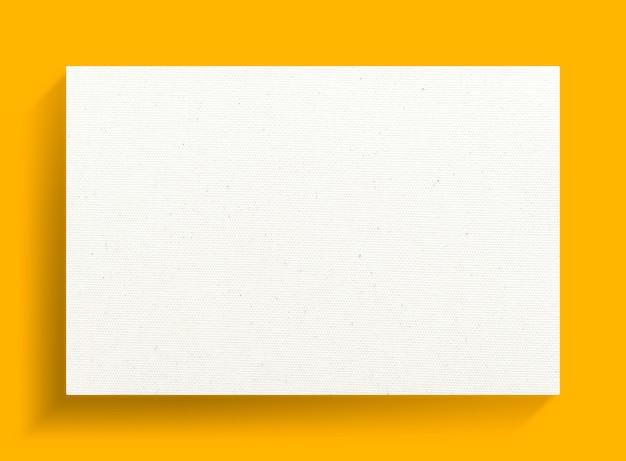 Quadro de lona branca sobre um fundo amarelo.