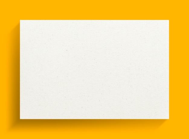Quadro de lona em fundo amarelo com sombra suave.