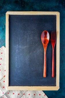 Quadro de lousa de menu na mesa de jantar com colher e folk