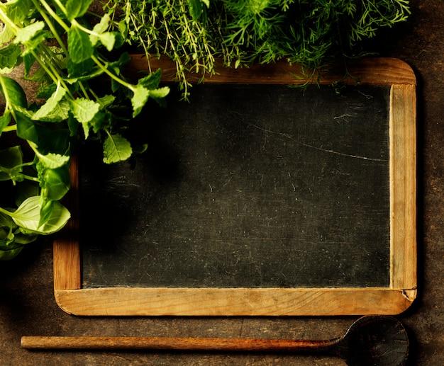 Quadro de lousa em branco com ervas, fundo copyspace