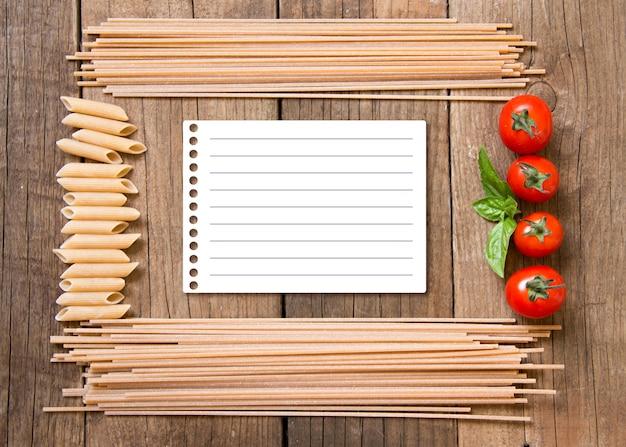 Quadro de macarrão espaguete, tomate e manjericão com papel na vista superior do plano de fundo de madeira