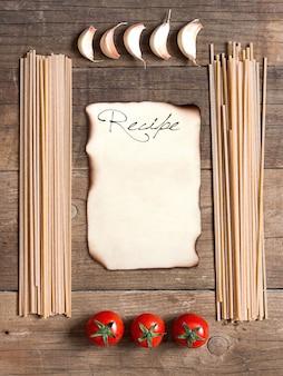 Quadro de macarrão, tomate e alho com espaço de cópia em papel na vista superior do plano de fundo de madeira