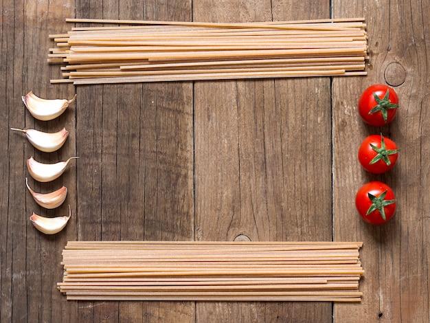 Quadro de macarrão, tomate e alho, com espaço de cópia na vista superior do plano de fundo de madeira
