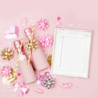 Quadro de maquete com garrafas de champanhe, confetes e decorações. dia dos namorados ou tema de conceito de festa de aniversário. camada plana, vista superior
