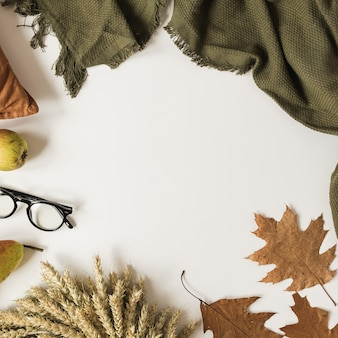 Quadro de mesa branca com estilo outono com cobertor, travesseiro, óculos, folhas secas de outono, peras, grinalda de palha de trigo.