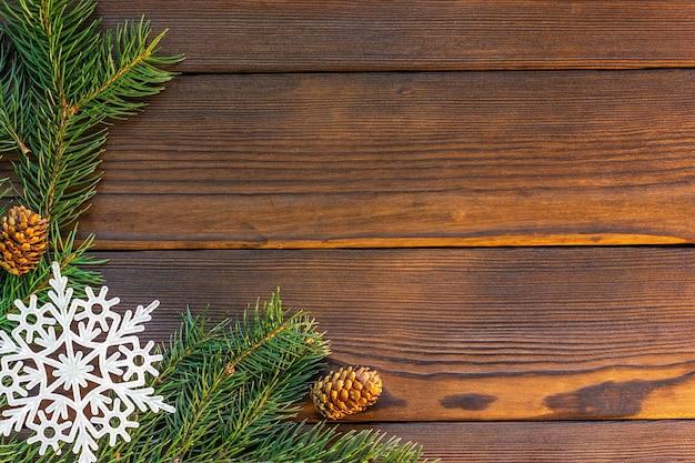 Quadro de natal com floco de neve de cones de ramos de abeto e presente vermelho em uma vista superior de mesa de madeira escura com ...