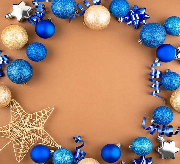 Quadro de natal de bolas azuis e douradas de ano novo, serpentina em um fundo marrom. copie o espaço.
