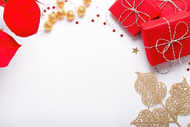 Quadro de natal festivo com flor de poinsétia vermelha, presentes embrulhados, decoração dourada e confetes na mesa branca, cópia espaço, vista superior. fundo de natal em vermelho e dourado