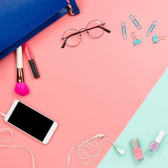 Quadro de negócios com a bolsa azul, óculos, smartphone, cosméticos e artigos de papelaria da mulher flexíveis.