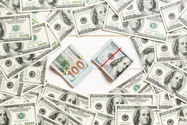 Quadro de notas de cem dólares com pilha de dinheiro