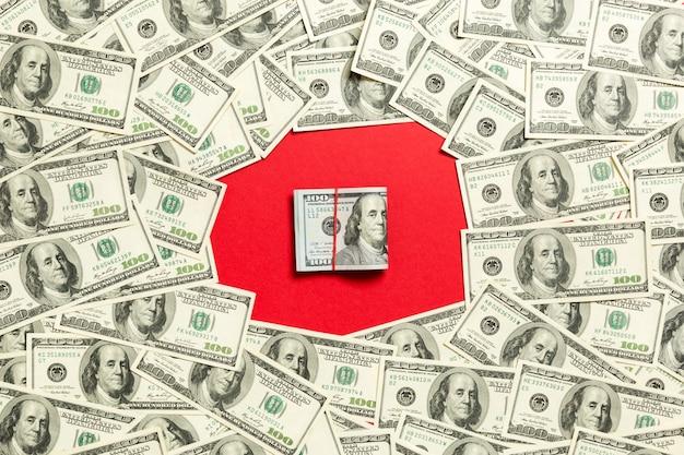 Quadro de notas de cem dólares com uma pilha de dinheiro no meio. vista superior do conceito de negócio em fundo vermelho, com espaço de cópia.