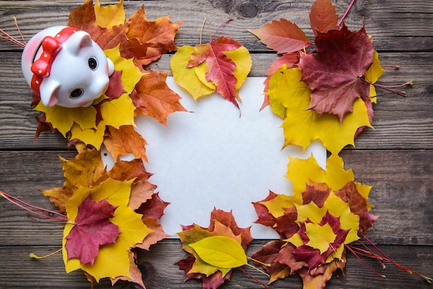 Quadro de outono com folhas amarelas, laranja, vermelhas e cofrinho em fundo de madeira com espaço de cópia