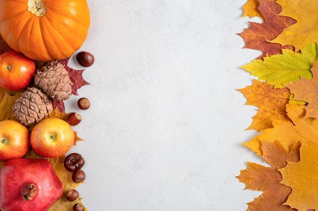 Quadro de outono com folhas de bordo amarelas, nozes, maçãs e abóbora. colheita de outono em plano de fundo cinza concreto com espaço de cópia.