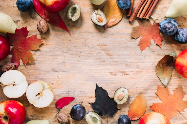 Quadro de outono com folhas e frutas em fundo de madeira