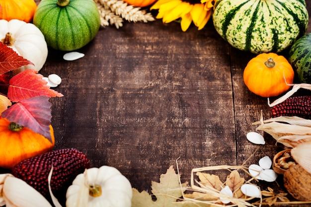 Quadro de outono de abóboras e milho na velha mesa de madeira. conceito do dia de ação de graças