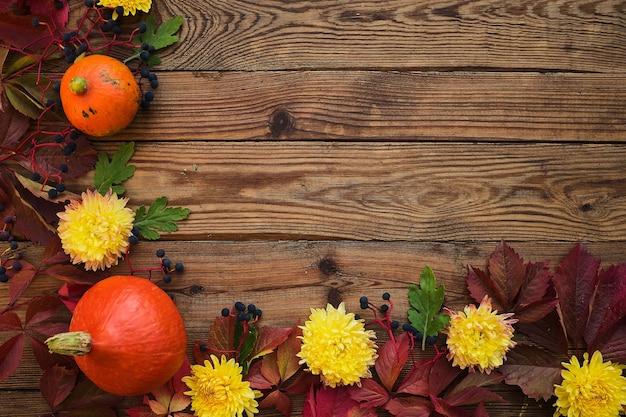 Quadro de outono - folhas vermelhas, abóboras, flores em uma vista superior do fundo de madeira escura. copie o espaço para inscrições, vista superior, espaço para texto. conceito de ação de graças.