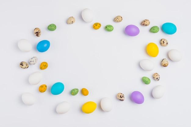 Quadro de ovos de páscoa coloridos na mesa branca