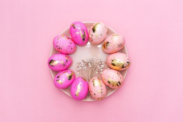 Quadro de ovos decorados dourados da páscoa no fundo do rosa pastel.