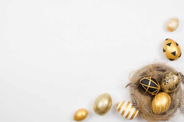 Quadro de ovos decorados dourados da páscoa no ninho isolado na superfície branca. conceito mínimo de páscoa.