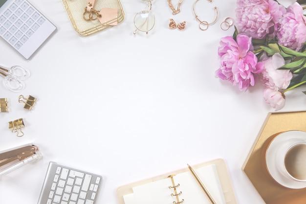 Quadro de papelaria ouro sobre fundo branco. diário, calculadora, caneca de café, grampeador, furador, caneta, óculos e teclado.