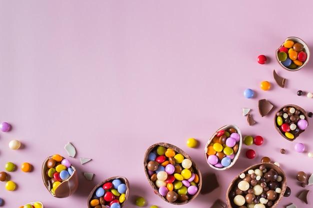 Quadro de páscoa com ovos de chocolate e doces em um fundo rosa. copiar espaço, vista superior, configuração plana