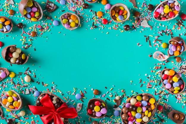 Quadro de páscoa com ovos de chocolate e doces em um fundo turquesa, verde e azul. copiar espaço, vista superior, configuração plana