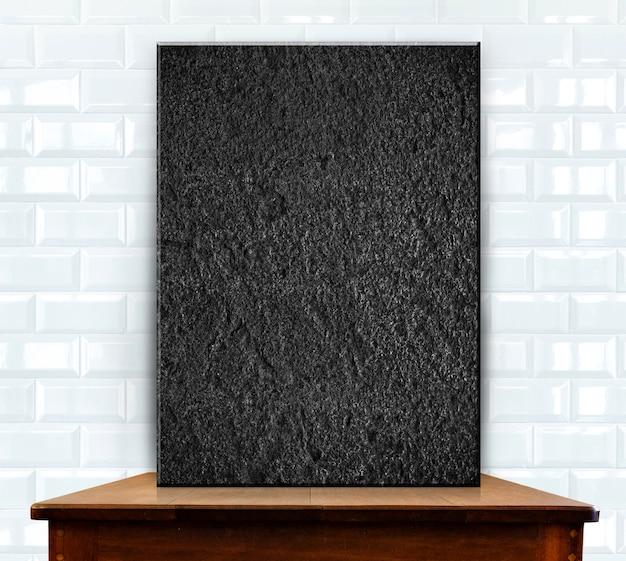 Quadro de pedra em branco na mesa de madeira na parede de cerâmica branca