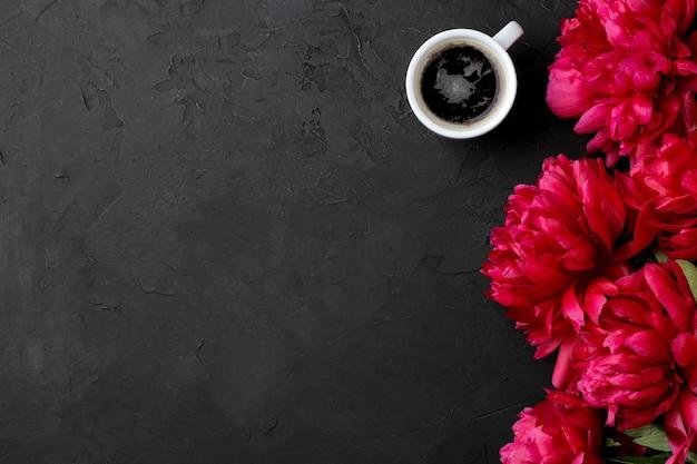 Quadro de peônias lindas flores rosa brilhantes e uma xícara de café em um fundo preto de grafite. vista do topo. espaço para texto
