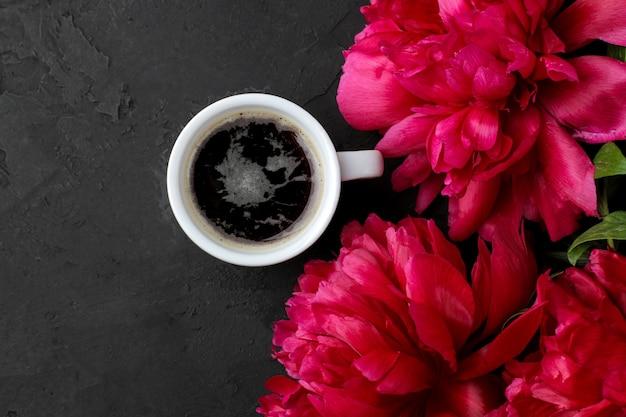 Quadro de peônias lindas flores rosa brilhantes e uma xícara de café em um fundo preto de grafite. vista do topo.