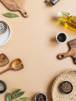 Quadro de pequenas tigelas diversas especiarias secas, utensílios de cozinha de madeira, azeite em frasco de vidro
