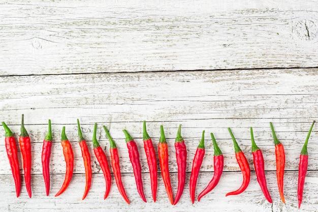 Quadro de pimenta vermelha do chile na mesa de madeira branca