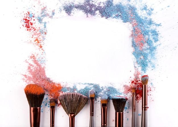 Quadro de pincéis de maquiagem com blush e sombra nos tons rosa, azul e coral