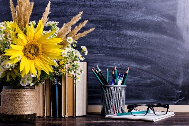 Quadro de placa de giz de madeira e buquê de vaso na mesa vazia