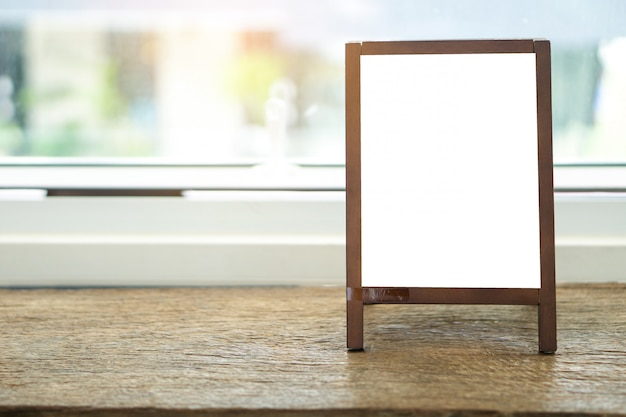 Quadro de publicidade em branco com pé de cavalete na mesa