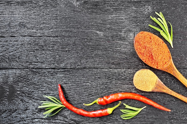 Quadro de raminhos de alecrim fresco, vagens de pimenta vermelha e duas colheres de pimenta moída