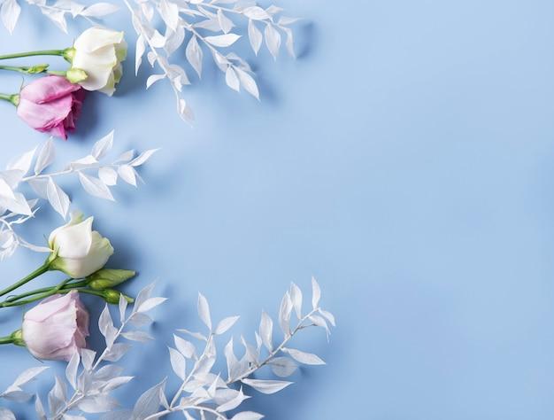 Quadro de ramos brancos com folhas e flores em uma parede azul