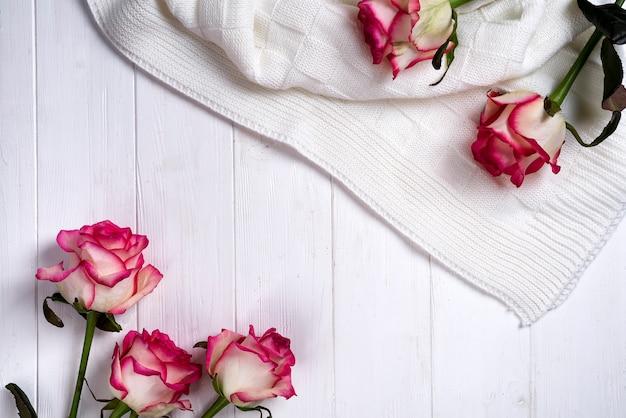 Quadro de rosas com manta no fundo branco de madeira