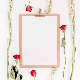 Quadro de rosas vermelhas e flores brancas com prancheta