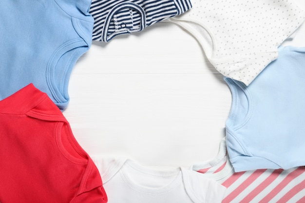 Quadro de roupas infantis em um fundo branco de madeira. lugar para texto