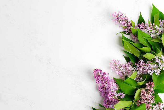 Quadro de saudação de flores frescas de lilás com folhas verdes, sobre um fundo de mármore cinza claro. vista do topo.