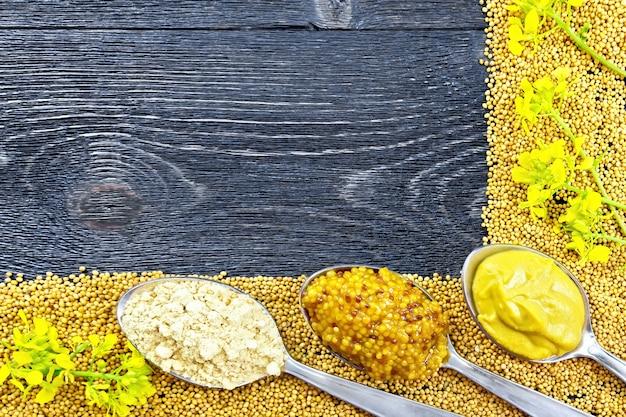 Quadro de sementes e flores de mostarda, mostarda e molho granulado, pó em colheres no fundo de uma placa de madeira preta