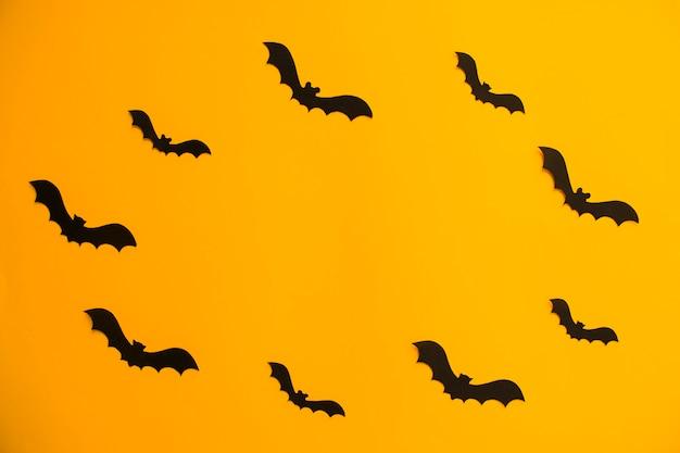 Quadro de silhuetas de papel de morcegos em fundo laranja. tratar ou enganar o halloween