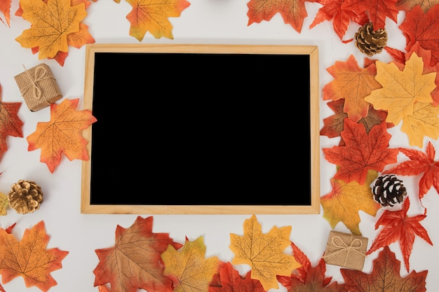 Quadro de superfície de madeira vista superior com folhas de bordo coloridas, cones, caixas de presente em branco