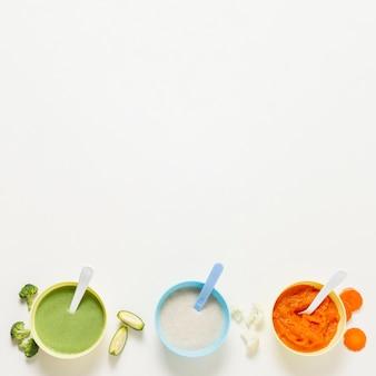 Quadro de tigelas de vista superior com comida para bebê