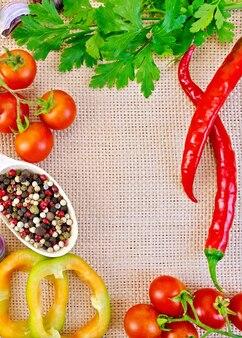 Quadro de tomates, pimentas doces e picantes, ervilhas, pimenta diferente na colher de pau, salsa e alho na sacaria